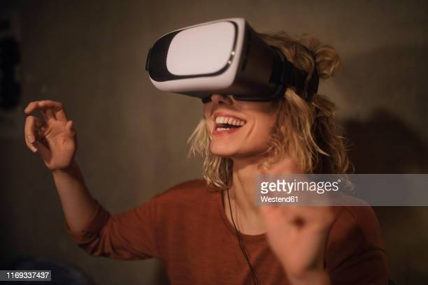 laughing young woman using virtual reality glasses at home - virtuelle realität stock-fotos und bilder