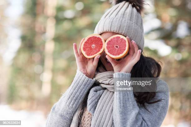 Laughing young woman wearing knitwear covering her eyes with halves of grapefruit