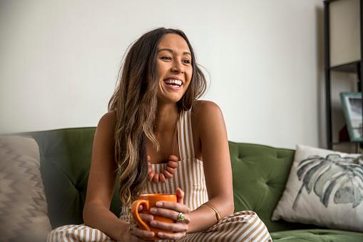 Laughing young woman with coffee mug sitting on couch - gettyimageskorea