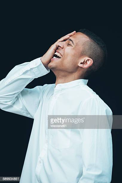 Laughing young woman with hand on his face wearing white shirt in front of black background