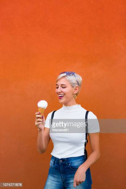 laughing young woman with ice cream cone in front of orange background - orange background stock pictures, royalty-free photos & images