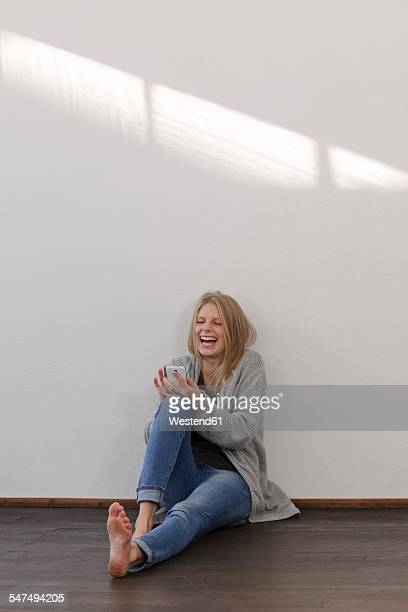 Laughing young woman with smartphone