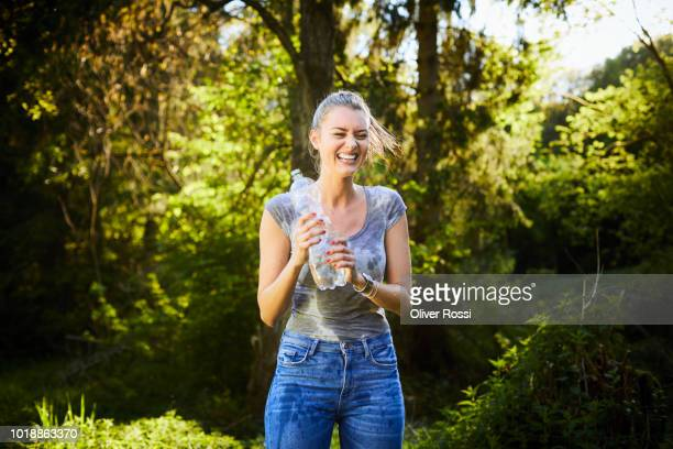 laughing young woman with wet clothes holding bottle of water - wet t shirts fotografías e imágenes de stock