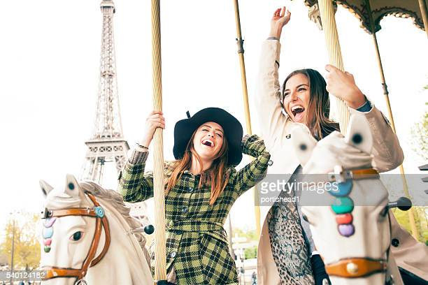 Laughing young women having fun on carousel at Eiffel Tower