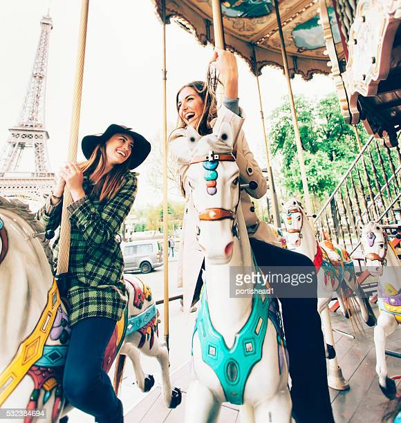 Laughing young women having fun on marry-go-round at Eiffel Tower