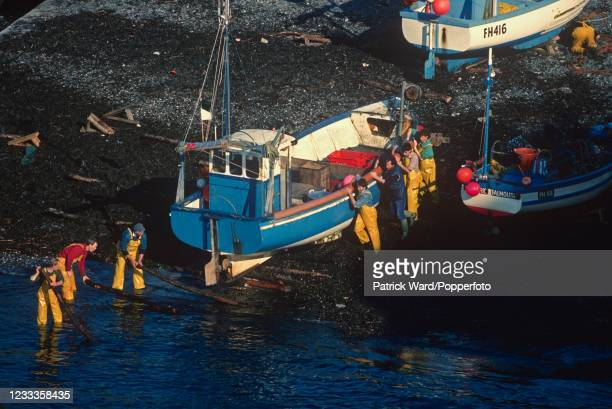 Launching a fishing boat in the harbour at Cadgwith, Cornwall, circa June 1989.