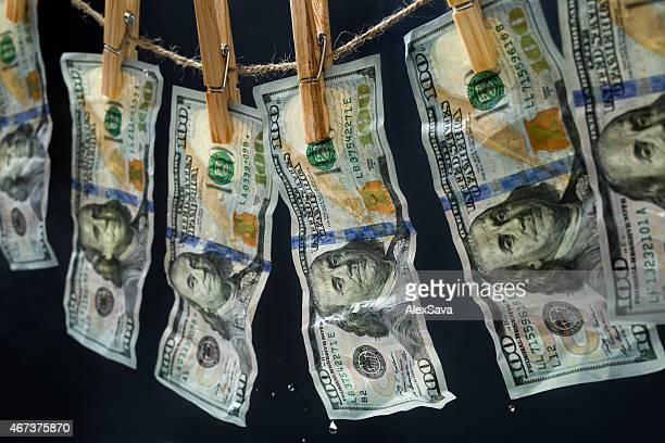 laundered dollars hanging on a rope - money laundering stock photos and pictures