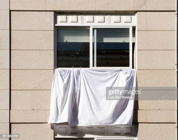 Laundry and bed sheets hang from building