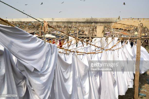 laundry at dhobi ghat - the magnificent washing wharf in karachi, pakistan with a huge garbage dump in the back - ghetto trash stock pictures, royalty-free photos & images