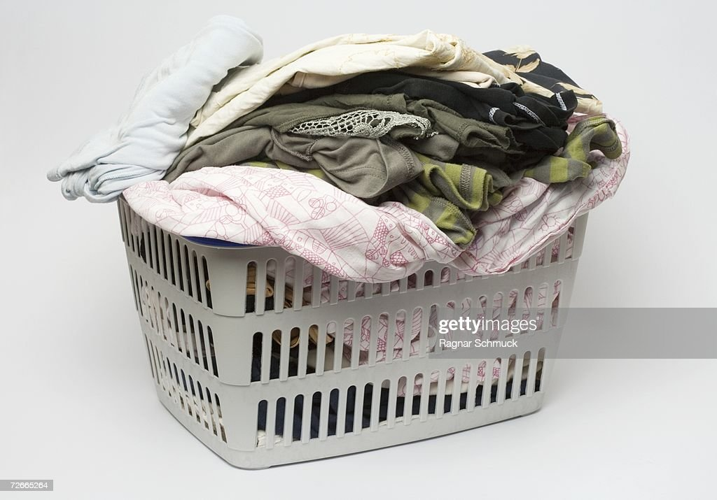Laundry basket full of clothes : Stock Photo