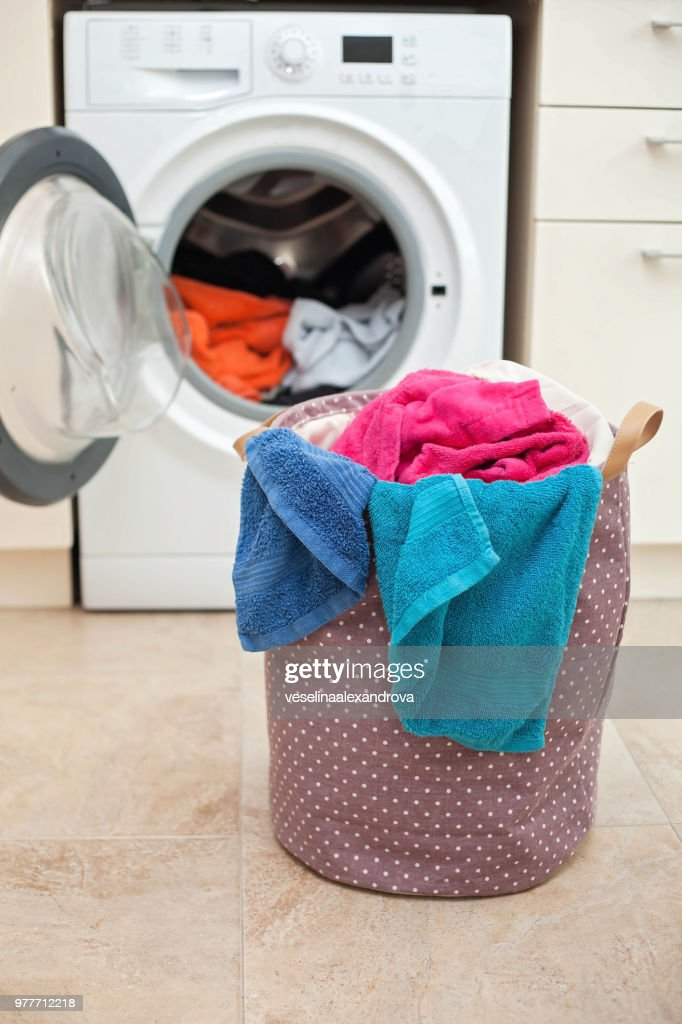 Laundry basket in front of a washing machine : Stock Photo