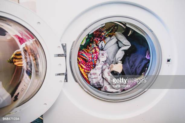 laundry day.washing machine full of colorful clothes - voll stock-fotos und bilder