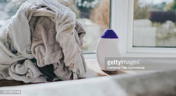 laundry detergent and pile of whites - weichspüler stock-fotos und bilder