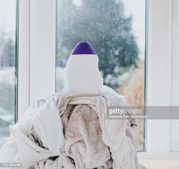 laundry detergent on top of a pile of whites - weichspüler stock-fotos und bilder