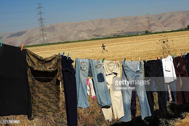 Laundry dries on a line inside of a camp for Syrians who have fled the fighting in their country on June 28 2013 in Baalbek Lebanon Baalbek which is...