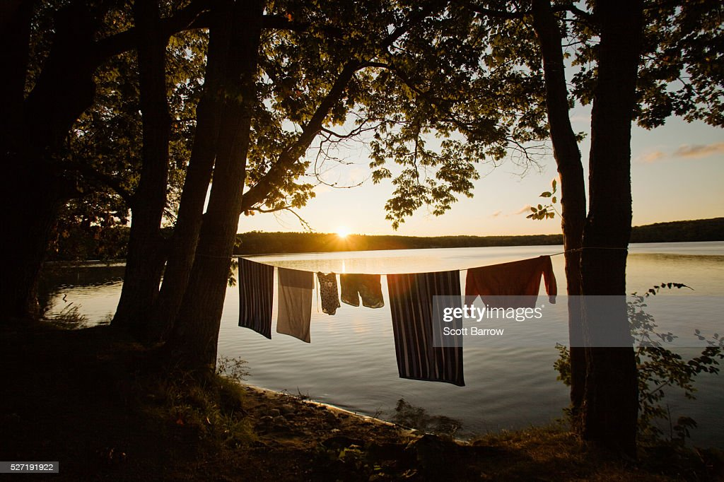 Laundry hanging on a line beside a lake : Stockfoto