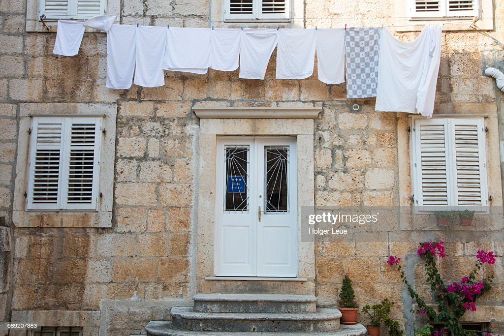 Laundry hangs from clothes line on brick building : Stock Photo