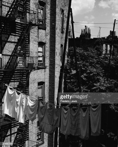 Laundry hangs on a clothesline stretched between apartment buildings on Bleecker Street Greenwich Village New York City 1960s