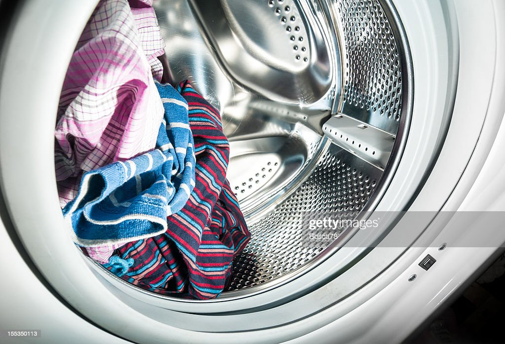Laundry inside a washing machine drum : Stock Photo
