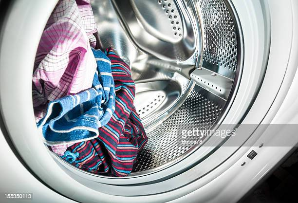 laundry inside a washing machine drum - washing machine stock pictures, royalty-free photos & images