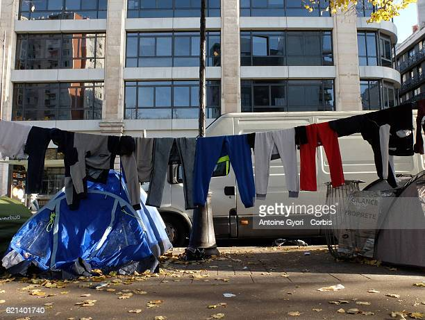 Laundry is hung as tents are pitched as migrants stand around near the Stalingrad metro station in a makeshift camp prior to the site being...