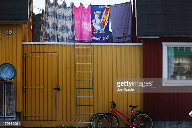 Laundry is hung to dry between homes on July 19, 2013 in Ilulissat, Greenland. As Greenlanders adapt to the changing climate and go on with their...
