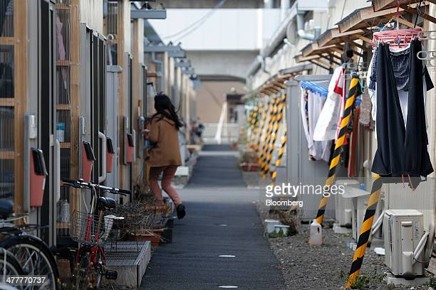 Laundry right hangs outside a temporary housing unit while a woman enters her housing unit at the Asutonagamachi temporary housing units in Sendai...