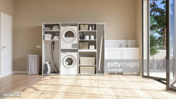 laundry room with beige wall and parquet floor with washing machine, dryer, laundry basket and folded towels in the cabinet. - washing machine stock pictures, royalty-free photos & images