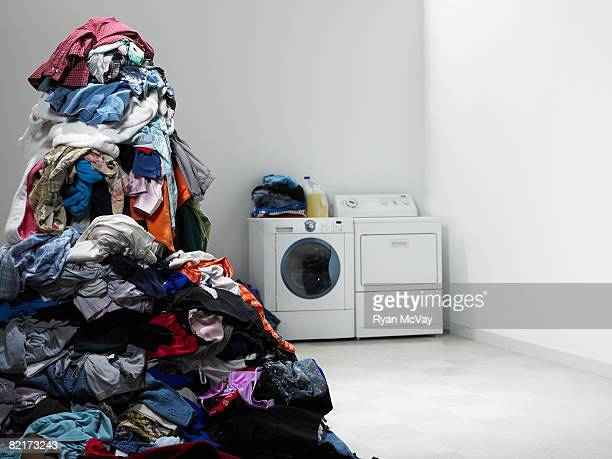 laundry room with tall pile of clothes. - heap stock pictures, royalty-free photos & images