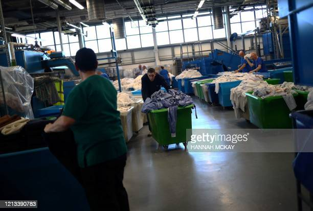 A laundry worker pushes a basket of gowns through the laundry and linen room at the Royal Blackburn Teaching Hospital in Blackburn northwest England...