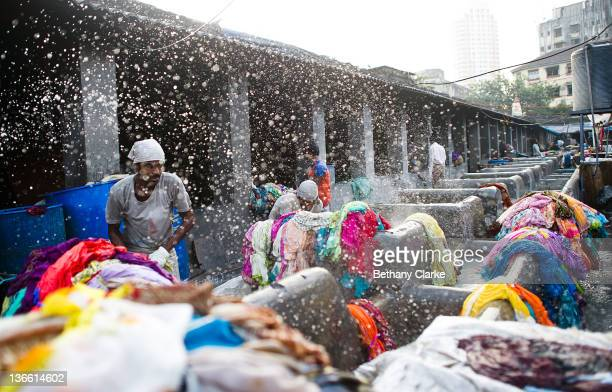 Laundry workers flog clothes at Dhobi Ghat on November 4 2011 in Mumbai India Dhobi Ghat is known as the world's largest laundry with 800 wash pens...