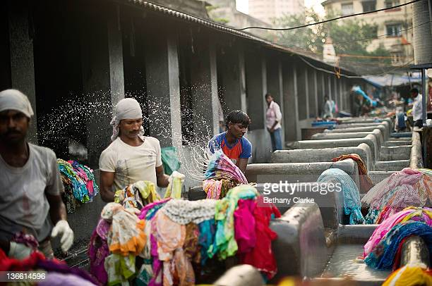 Laundry workers wash clothes at Dhobi Ghat on November 4 2011 in Mumbai India Dhobi Ghat is known as the world's largest laundry with 800 wash pens...