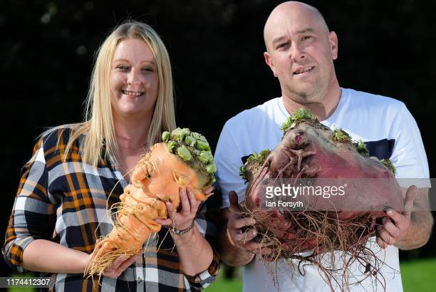 Laura and Chris Marriott pose during a press photo call with their winning carrot at 38kg and Beetroot at 17840kg following judging for the giant...