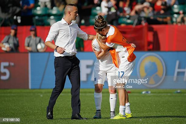 Laura Bassett of England is comforted by Jo Potter and England manager Mark Sampson after the FIFA Women's World Cup Semi Final match between Japan...