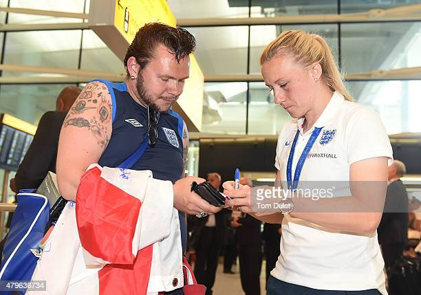 Laura Bassett of the England Women's team signs autographs after arriving back from the World Cup at Heathrow Airport on July 6 2015 in London England