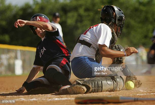 Laura Berg of the USA Olympic Softball Team slides safely into home plate against a dropped ball by Christy Delarosa of the Ft Worth AllStars in the...