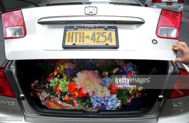 Laura Bopp stows her homemade flower hat in her car's trunk in Midtown after the annual Easter Parade on April 21 2019 in New York City Each year New...