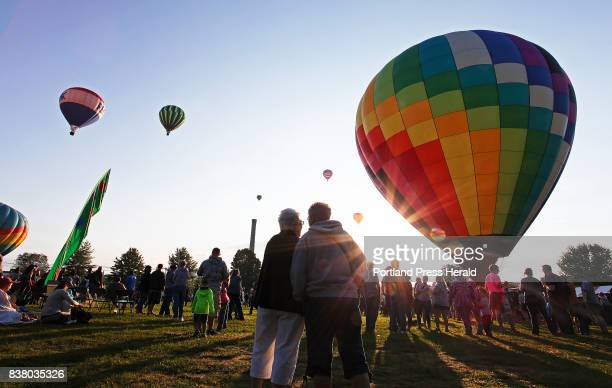 Laura Buker and Karen Ryder of Augusta center watch as balloons take flight from Simard Payne Park early Sunday morning at the Great Falls Balloon...