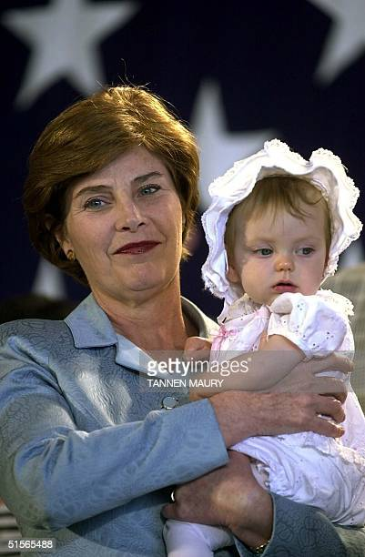 Laura Bush holds 9monthold Krista Dye as Republican presidential nominee Texas Gov George W Bush addresses a rally at the Spokane airport in Spokane...