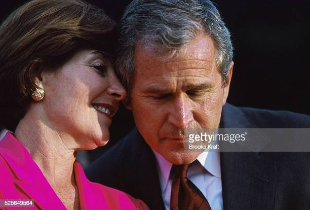 Laura Bush whispers to her husband, Republican presidential candidate George W. Bush, on the campaign trail. Texas Governor Bush was campaigning for...