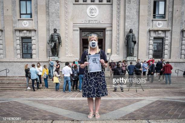 Laura Capella shows a photo of her father who died of Covid-19 in front of the Public Prosecutors office in Bergamo, where she just filed a formal...
