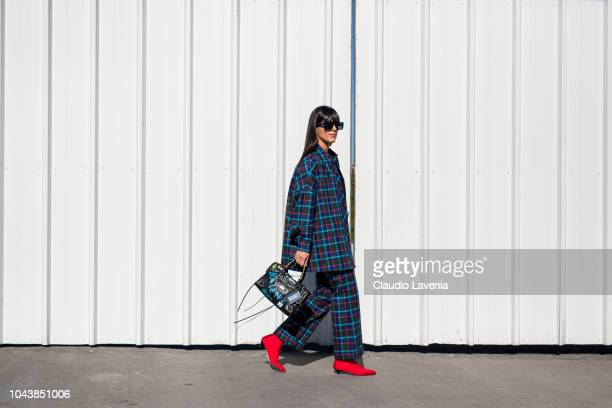 Laura Comolli, wearing black top, backed jacket with matching pants, red boots and Balenciaga bag, is seen before the Balenciaga show on September...