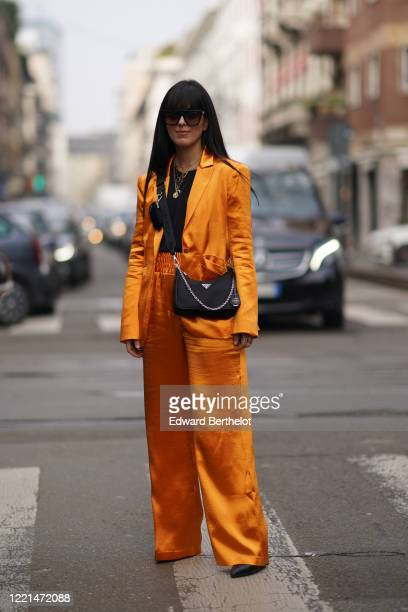 Laura Comolli wears sunglasses, a lustrous shiny orange jacket, a Prada bag, flared pants, a necklace, outside Calcaterra, during Milan Fashion Week...