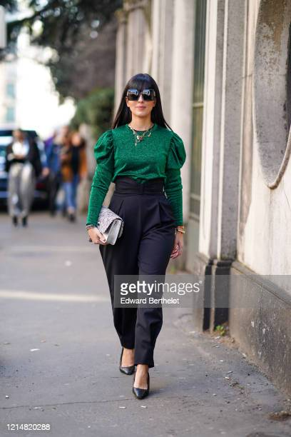 Laura Comolli wears sunglasses, necklaces, bracelets, a heather forest-green top with puff sleeves, high-rise black pleated pants, black pointy...