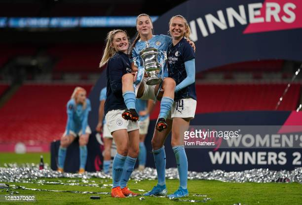 Laura Coombs, Jess Park, and Esme Morgan of Manchester City celebrate with the Vitality Women's FA Cup Trophy following their team's victory in the...