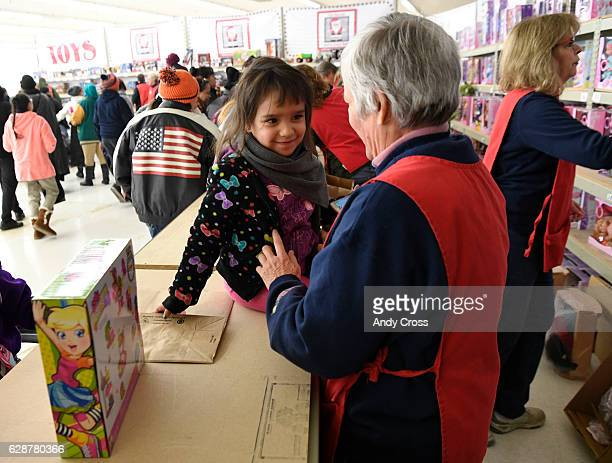 Laura Escobedo left gives volunteer Cynthia Herndon a smile after Herndon helped her pick out a doll at the 86th annual Denver Santa Claus Shop at...