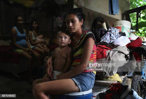 Laura Guevara holds her son Emerson 14 months outside her oneroom home in an impoverished neighborhood on August 19 2017 in San Pedro Sula Honduras...