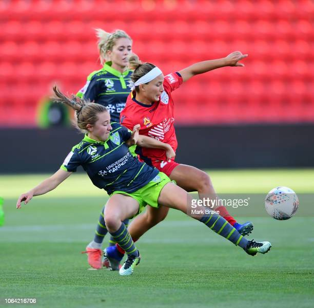 Laura Hughes of Canberra United competes for the ball against Amber Brooks of Adelaide United during the round four WLeague match between Adelaide...