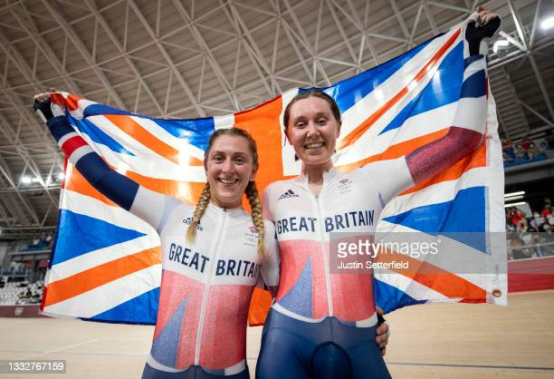 Laura Kenny and Katie Archibald of Team Great Britain celebrate winning a gold medal while holding the flag of their country during the Women's...