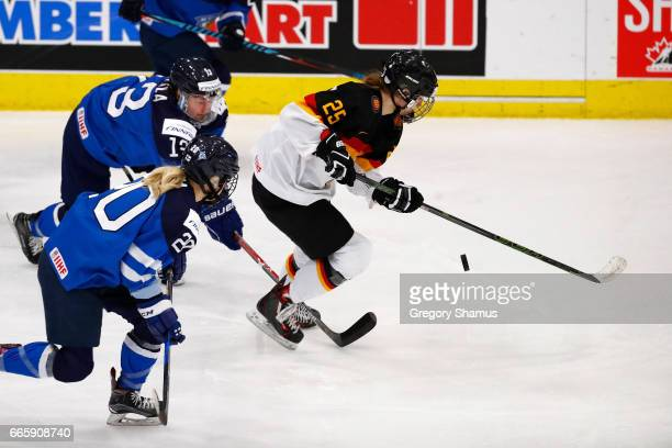 Laura Kluge of Germany tries to control the puck in front of Riikka Valila of Finland during the first period in the bronze medal game at the 2017...